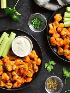 Close up of Buffalo Cauliflower Bites on a black plate with a ramekin of Creamy Dill Dip and a side of celery stalks.