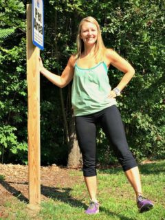 Blonde woman wearing a green tank top and black leggings holding a pole demonstrating a dynamic stretch.