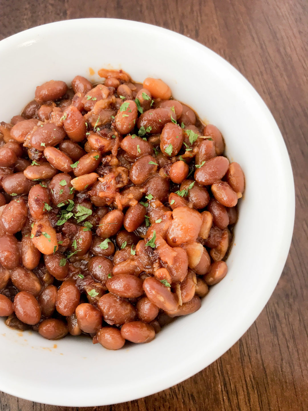 These Instant Pot BBQ Brown Sugar Baked Beans may be one of the easiest recipes I've ever cooked. You literally just dump all of the ingredients into the Instant Pot and walk away. No fuss, no muss.  This is an adaptation of my husband's crockpot beans, but instead of taking 6 hours to make, they only take an hour in the Instant Pot! #instantpotrecipe #bbqrecipe #brownbeans #tailgating