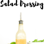 Zesty lime salad dressing in a bottle on a wooden board with white bowl of spinach and cut lime slices, zesty lime salad dressing text overlay