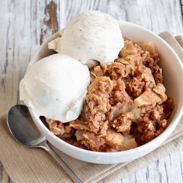 Fresh hot homemade apple crisp or crumble with crunchy streusel topping topped with vanilla bean ice cream. Selective focus with blurred background.