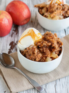 Fresh hot homemade apple crisp or crumble with crunchy streusel topping topped with vanilla bean ice cream and Caramel Sauce. Selective focus with blurred background.