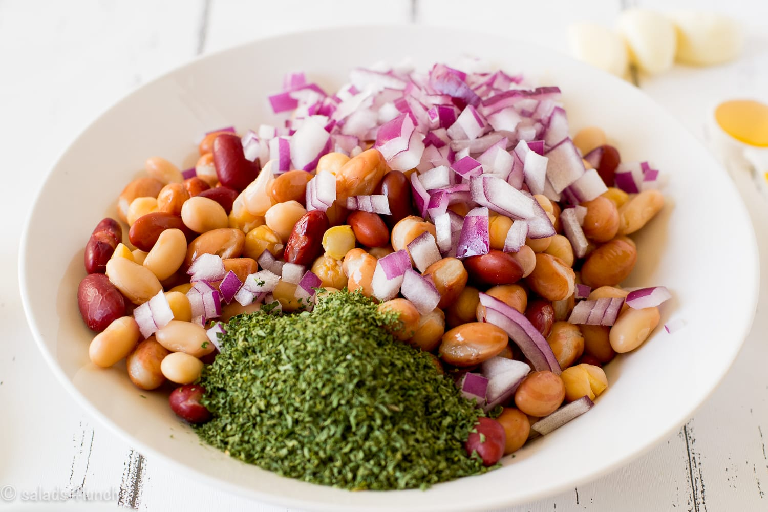 Close up of a white bowl on a white wood background with mixed beans, minced cilantro and red onion in it.