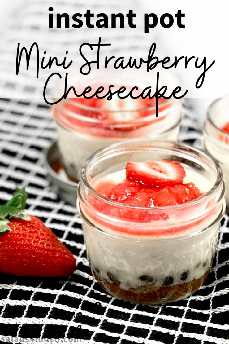 "Close up of strawberry cheesecake in a mini mason jar with text overlay that says ""Instant pot mini strawberry cheesecake""."