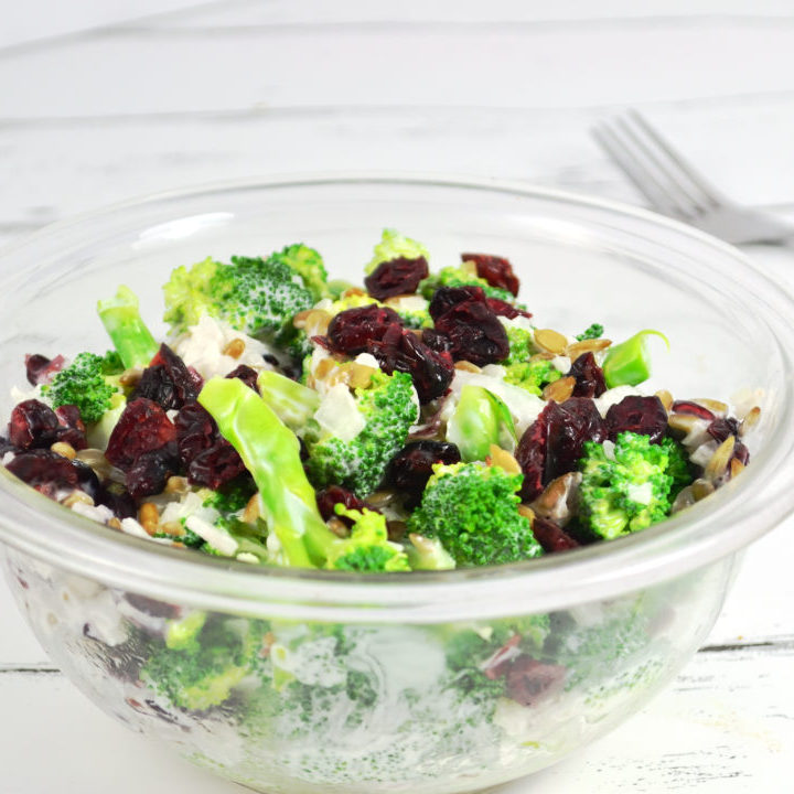 Bowl of healthy broccoli salad with fork in the background.