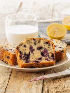 Three slices of blueberry lemon loaf on a white plate with a glass of milk and a sliced lemon in the background.