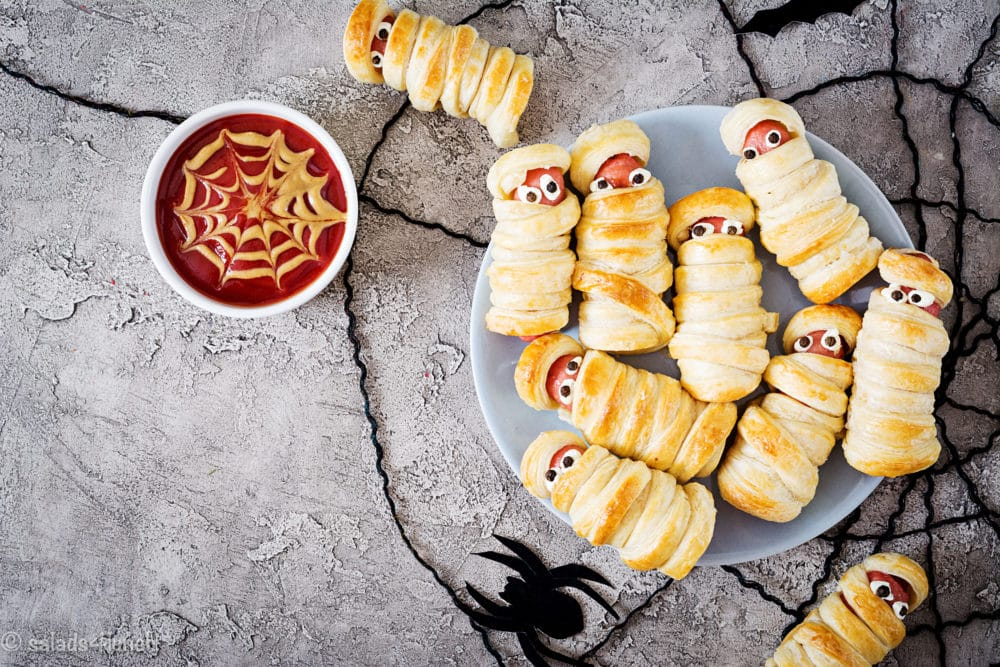Every Halloween Party needs a silly Mummy – this Mummy Hot Dog Recipe is a fun kitchen food craft for the kids and will be a party favourite. #halloweenrecipe #kidsfoodcraft #foodcraft #halloweentreat #halloweenparty