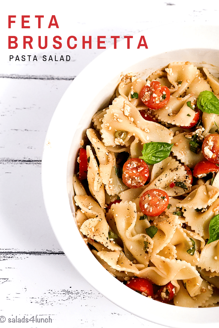 White bowl of bow tie feta bruschetta pasta salad with sprig of basil and roma tomatoes.