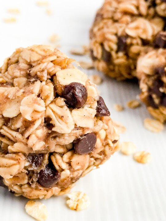 Close up of a peanut butter oate=meal banana and chocolate energy ball on a white plate