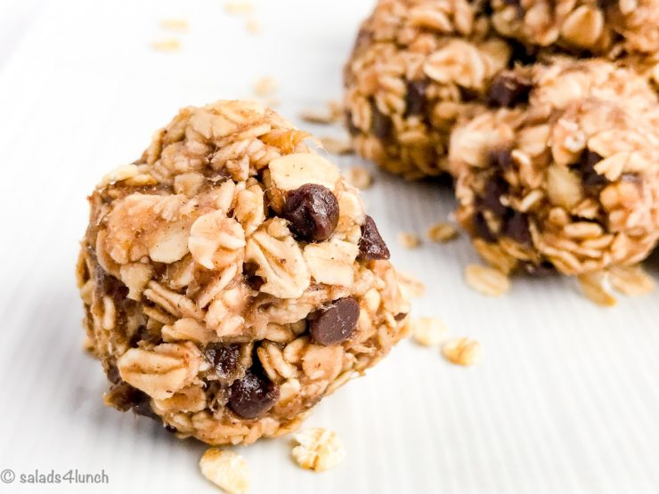 close up of a peanut butter banana oatmeal and chocolate chipe energy ball on a white plate.