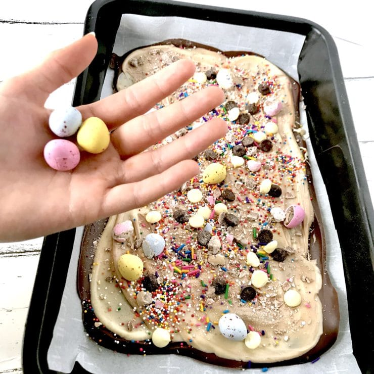 Chocolate Easter Bark in a pan with a hand holding Cadbury Mini Eggs