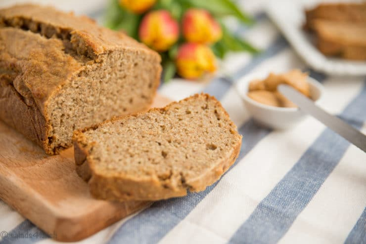 Sliced banana bread with flowers and butter in the background.