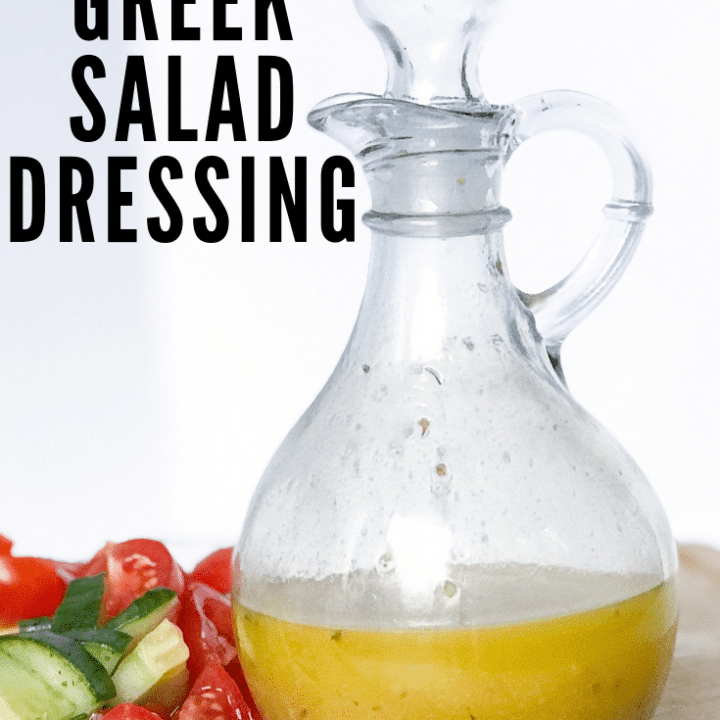 Photo of greek salad dressing in glass jar with tomatoes and cucumbers