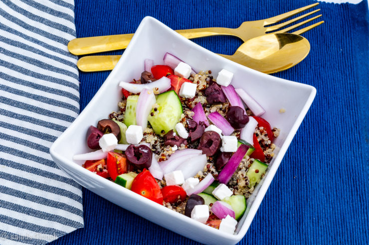 Close up of square white bowl full of colourful greek quinoa salad on blue placemat with blue and white striped napkin and gold cutlery