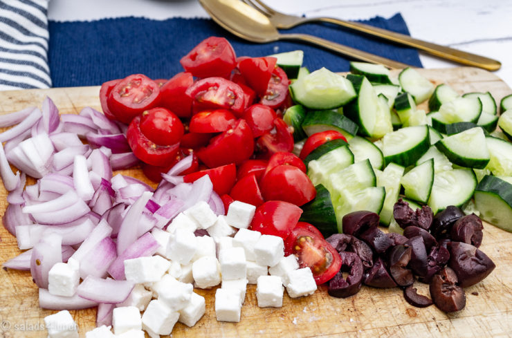 Close up of cut tomatoes, cucumber, black olives, feta cheese and red onion on an oak cutting board