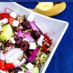 """Close up of square white bowl of colourful greek quinoa salad in a white bowl with """"Greek Quinoa Salad"""" text overlay"""