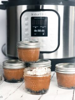 Stacked mini mason jar chocolate cheesecakes in front of an Instant Pot