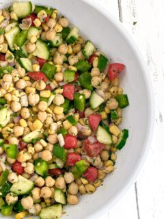 Cilantro lime chickpea salad in a white bowl on white wood countertop