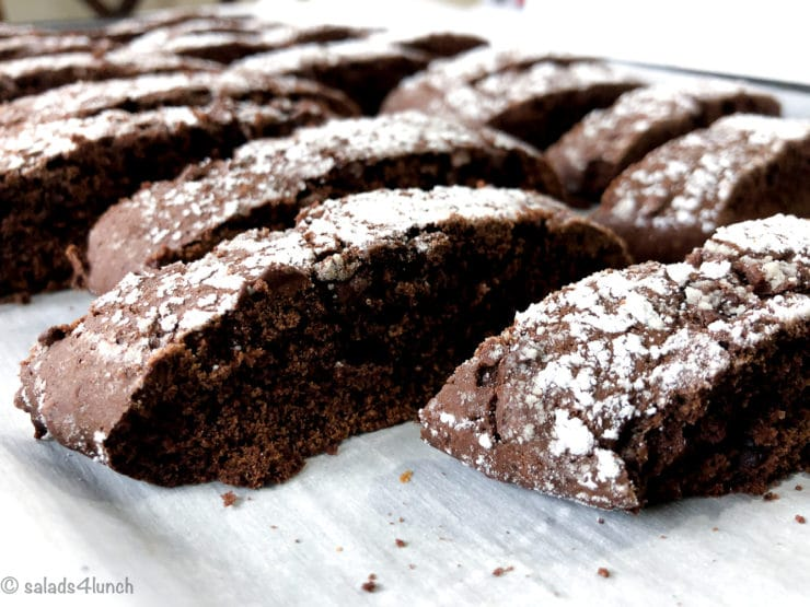 Close up of double chocolate biscotti on a baking sheet lined with parchment paper
