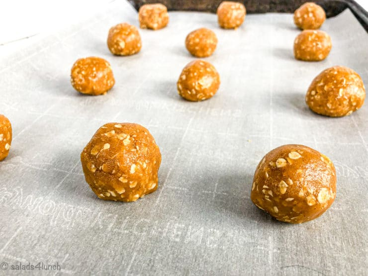 Balls of peanut butter oatmeal cookies on a baking sheet lined with parchment paper.