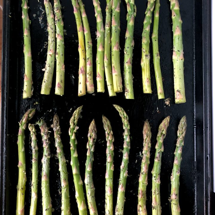Sheet pan of perfectly roasted asparagus stalks.