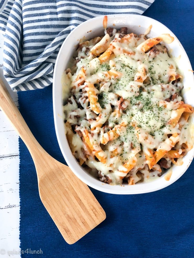 Penne pasta with hearty meat sauce with melted mozzarella cheese in a white casserole dish on a blue background