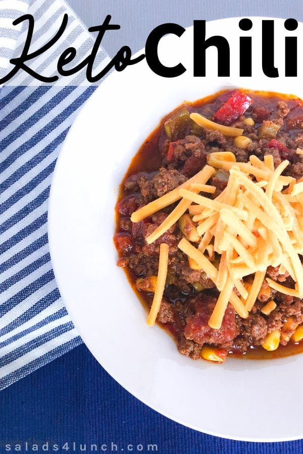 Overhead of of keto chili toppped with cheese in white bowl on blue placemat.