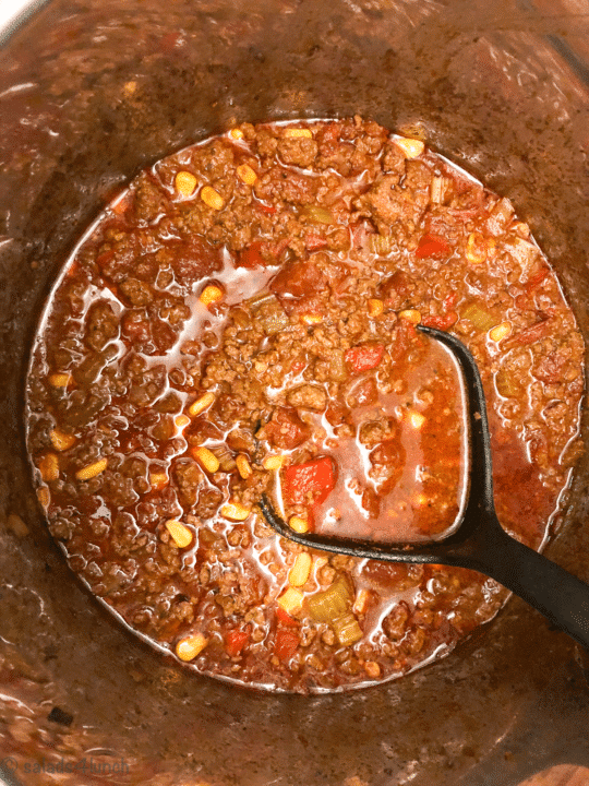 Keto chili simmering in a pot with black ladle