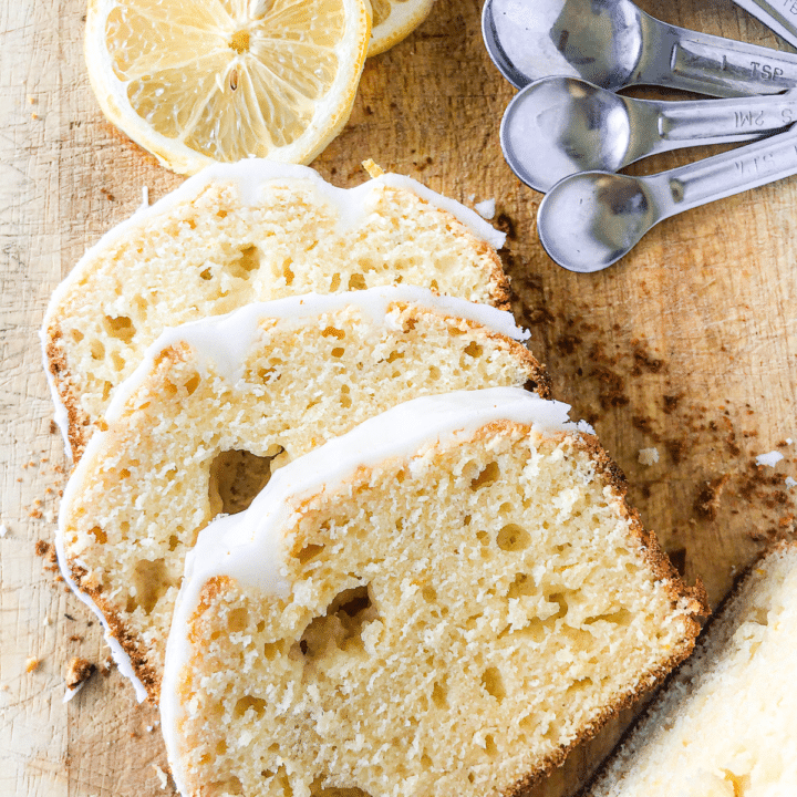 Overhead photo of wooden cutting board with three slices of lemon loaf drizzled with a white lemon icing