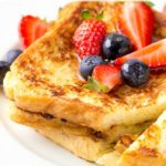 "Two slices of Classic french toast with blueberries and strawberries on a white plate, with ""Classic French Toast"" text overlay."