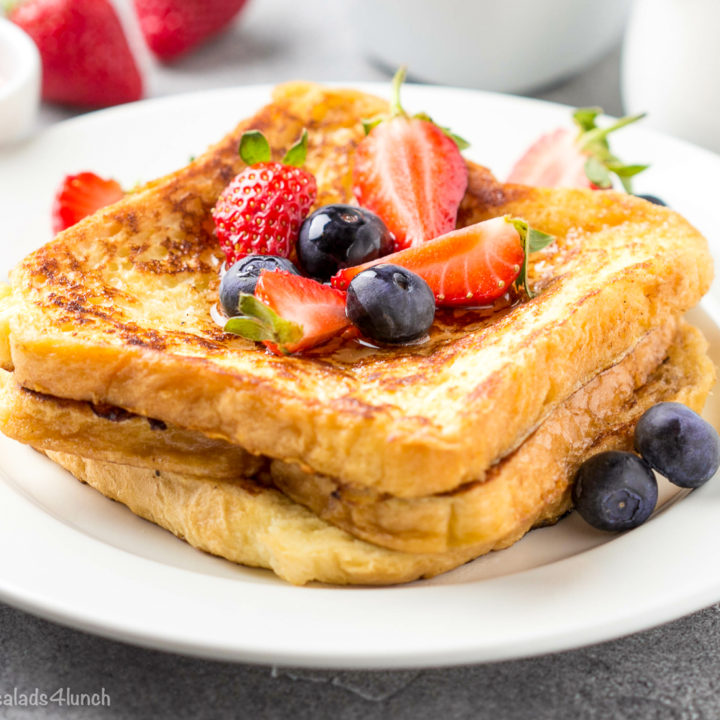 Two slices of Classic french toast with blueberries and strawberries on a white plate.