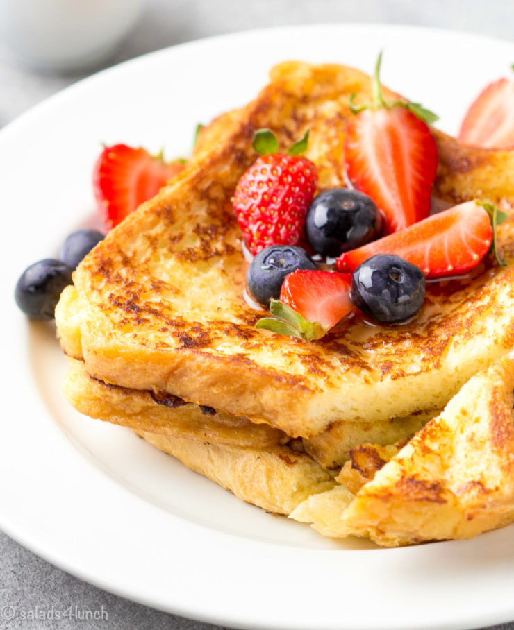 French toast with berries (blueberries, strawberries) and sauce, traditional sweet dessert of bread with egg and milk. Morning baking food.