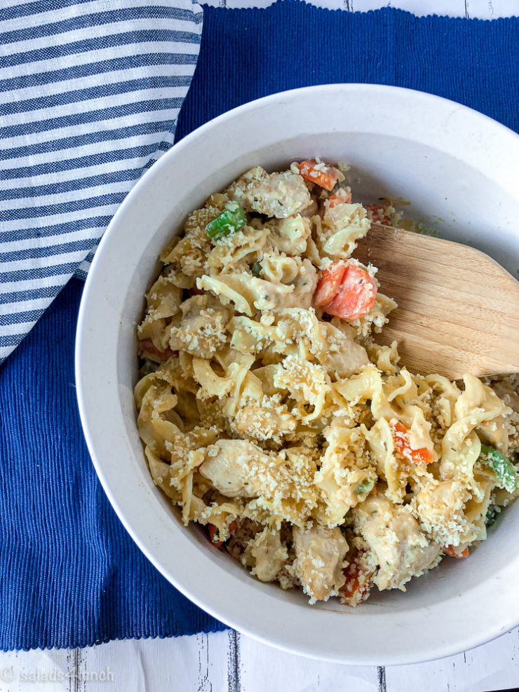 White casserole dish on a blue placemat with blue striped napkin with creamy chicken noodle casserole loaded with tender carrots and celery.