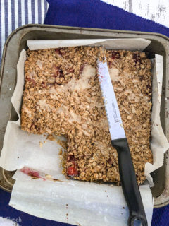 Closeup of Blueberry and Strawberry Oatmeal Crumble Bars in a square pan with one piece missing and a knife on the pan with a blue and white napkin beside it.