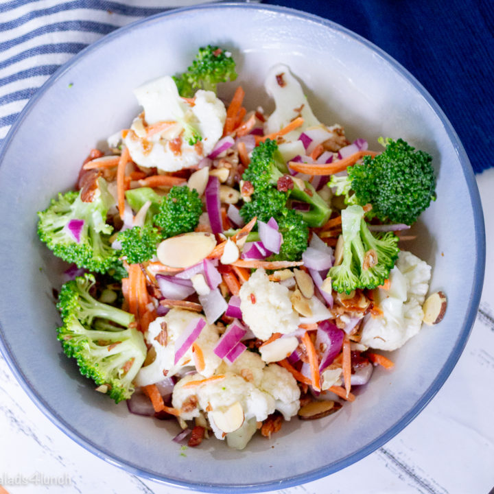white bowl of broccoli and caulflower florets with chopped red onion, bacon bits, and matchstick carrots