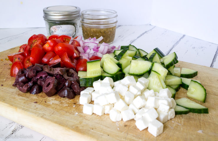 Wood cutting board with chopped up red onions, cucumbers, cherry tomoatoes, cubed feta cheese and black olives with greek salad dressing in a jar in the background.