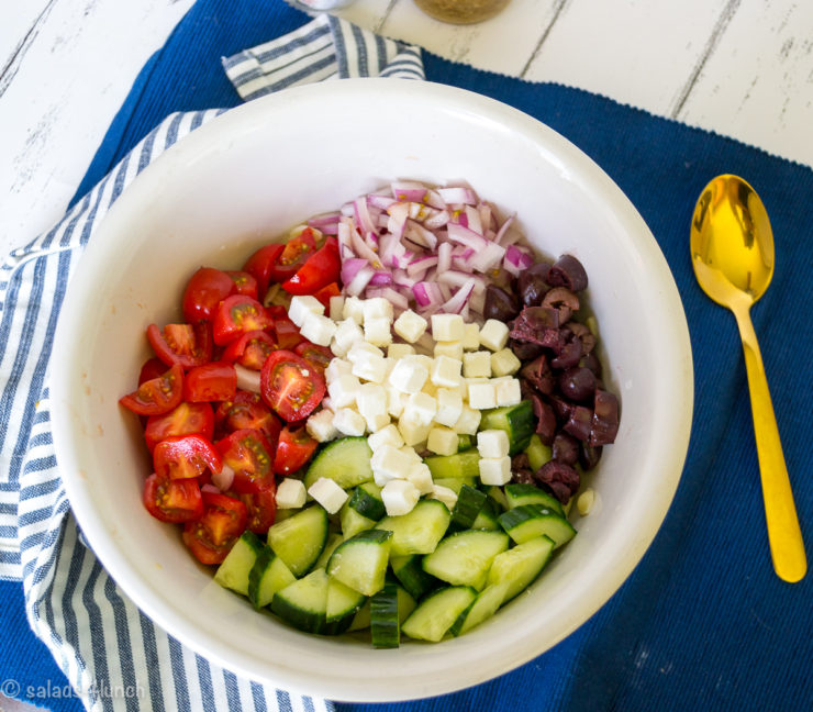 Large white salad bowl with chopped up red onions, cucumbers, cherry tomoatoes, cubed feta cheese and black olives with greek salad dressing in a jar in the background.