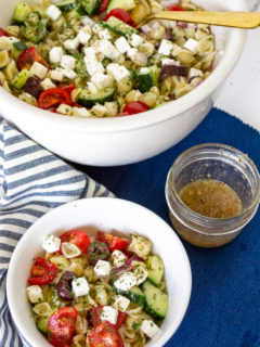 Large white bowl and smaller white bowl of colourful greek pasta salad with a small jar of greek dressing on a blue placemat