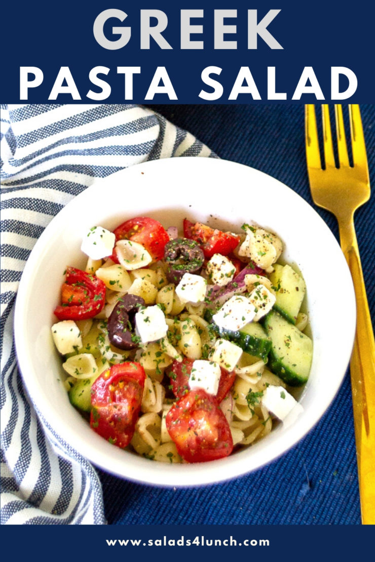 "White bowl of Greek Pasta Salad loaded with cubed feta cheese, black olives, red tomatoes, red onions and cucumbers with ""Greek Pasta Salad"" text overlay"