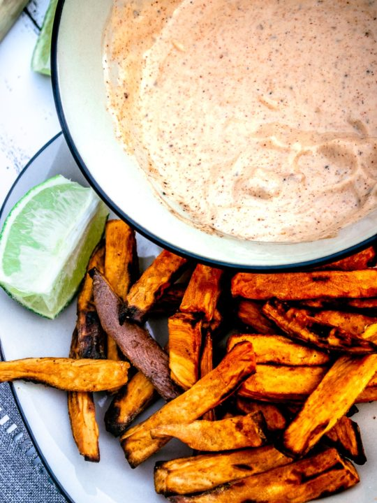 Plate of delicious sweet potato fries made in the air fryer with a bowl of chipotle may in the background