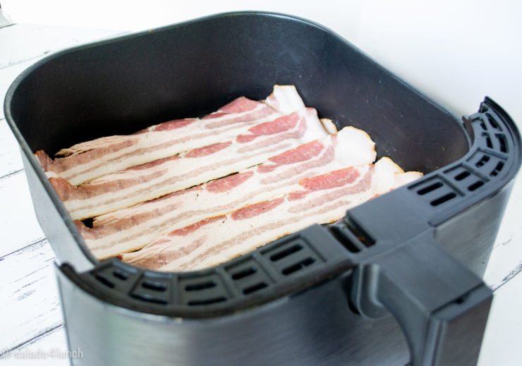 Raw bacon strips in an air fryer basket