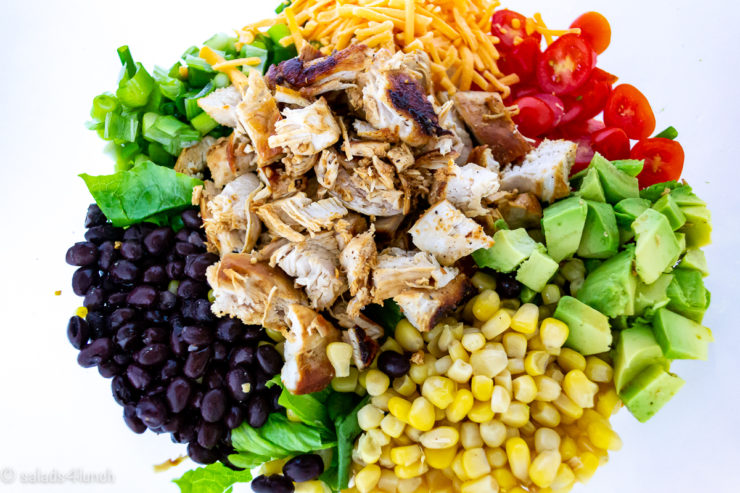 Large white bowl of Chiptle Chcicken Salad ingredients: chicken, avocado, corn, cheese, romaine lettuce, black beans and avocado