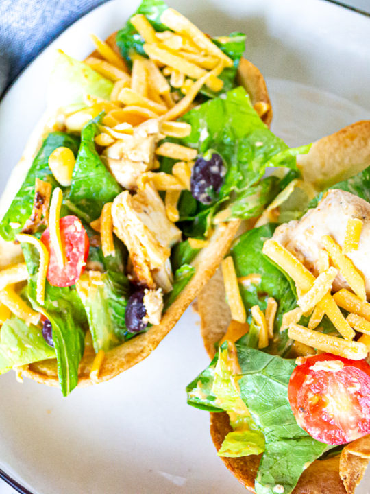 Two crispy edible taco bowls with chipotle chicken salad in them on a square white plate with black trim and a grey napkin beside the plate.