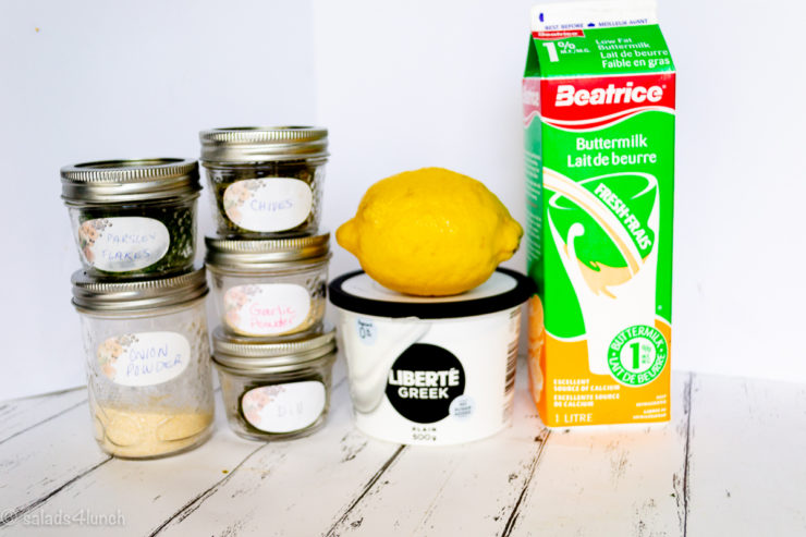 Ingredients you'll need to make homemade ranch dressing: greek yogurt, buttermilk, chives, onion powder, garlic powder, dill, lemon, salt & pepper. All spices are in mini mason jars stacked on each other.