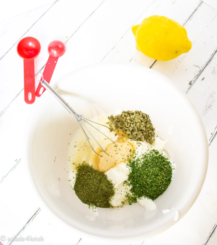 White mixing bowl and whisk showing the ingredients you'll need to make greek yogurt ranch dressing: Ingredients you'll need to make homemade ranch dressing: greek yogurt, buttermilk, chives, onion powder, garlic powder, dill, lemon, salt & pepper.