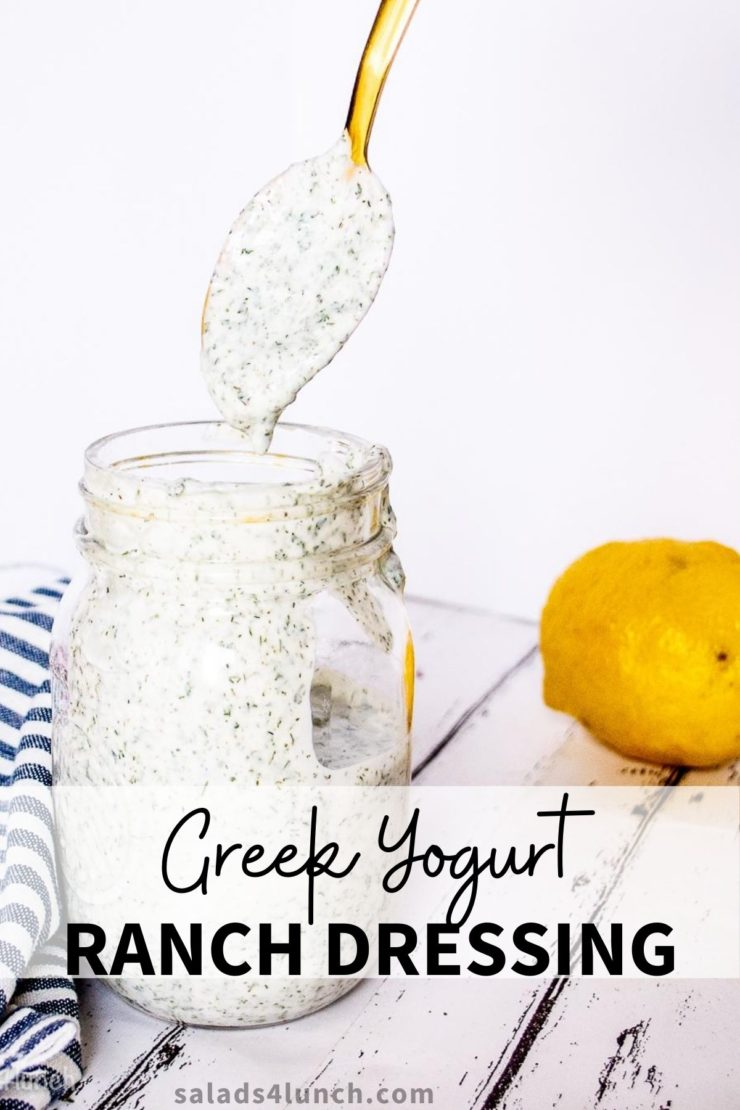 Gold spoon drizzling ranch dressing into a glass mason jar of creamy white ranch dressing on a white washed wood board. A blue and white striped napkin and lemon can be seen in the background.