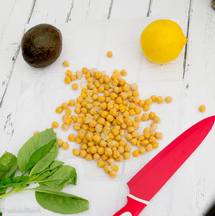Photo of an avocado, lemon, chickpeas and spinach on a white wooden background.