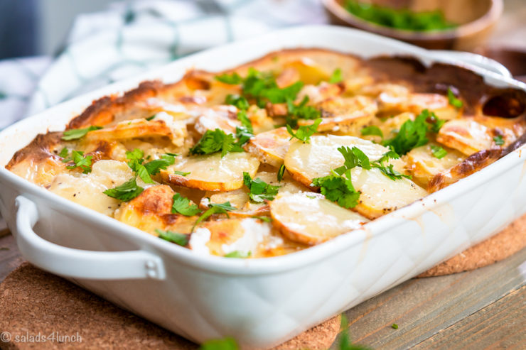 "Baked scalloped potatoes garnished with fresh cilantro with text overlay that reads ""Easy Creamy Scalloped Potatoes""."