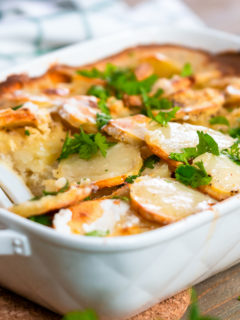 Baked scalloped potatoes garnished with fresh cilantro.