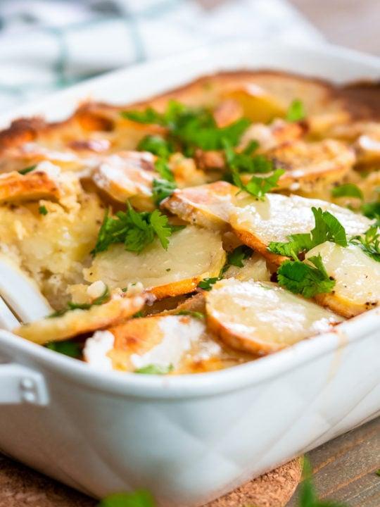 Baked scalloped potatoes garnished with fresh cilantro.